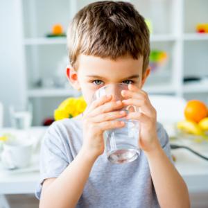 Petit garçon qui boit de l'eau en regardant la caméra