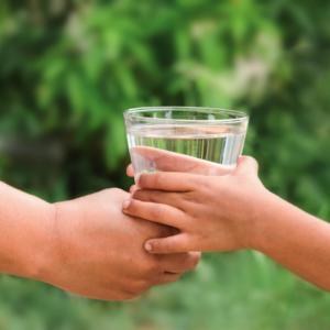 Main d'adulte tendant un verre d'eau à une main d'enfant